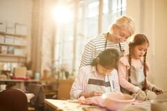 Two Little Girls in Pottery Class. Portrait of smiling art teacher helping two little girls in pottery class, copy space stock photography
