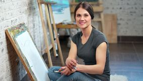 Portrait of smiling artist woman posing at art studio looking at camera medium shot. Happy female painter enjoying break during drawing illustration on canvas stock footage