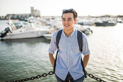 Portrait of smiling asian man near sea boats in the old european city. Tourist. Portrait of smiling asian man near sea boats in the old european city Stock Image