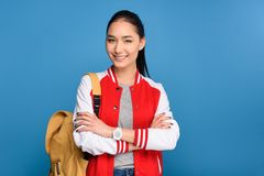 Portrait of smiling asian student with backpack. Isolated on blue royalty free stock image