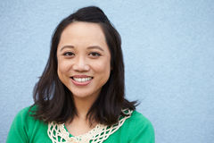 Portrait of smiling Asian woman against grey wall Royalty Free Stock Photos