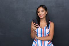 Portrait of a smiling asian woman in dress standing isolated over gray background,. Using moible phone royalty free stock images