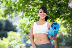 Portrait of smiling athletic woman carrying yoga mat Royalty Free Stock Photo