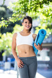 Portrait of smiling athletic woman carrying yoga mat Stock Image