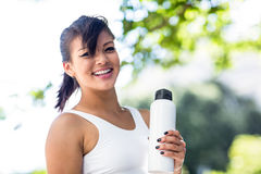 Portrait of smiling athletic woman holding water bottle and looking at camera Stock Image