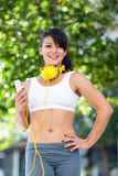 Portrait of smiling athletic woman wearing yellow headphones and holding smartphone Stock Photos
