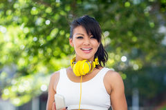 Portrait of smiling athletic woman wearing yellow headphones and holding smartphone Royalty Free Stock Photo
