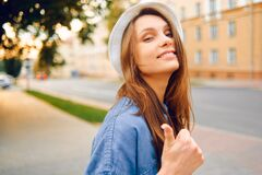 Portrait of a smiling girl in a white hat and a blue denim shirt on a background of a sunset city