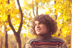 Portrait of smiling attractive man dressed in striped sweater, oudoor in autumn park. Stock Photos