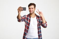 Portrait of a smiling attractive man taking a selfie. While standing and showing peace gesture isolated over white background royalty free stock photos