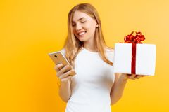 Portrait of smiling attractive woman, holding gift box, standing and using mobile phone, isolated on yellow background royalty free stock photo