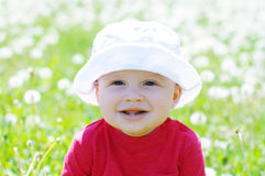 Portrait of smiling baby against blowballs Royalty Free Stock Photo