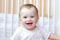 Portrait of smiling baby against white bed. Portrait of smiling baby age of 11 months against white bed Royalty Free Stock Photography