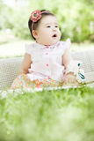 Portrait of a smiling baby. An Asian baby is sitting on grass and smiling innocently Stock Photography