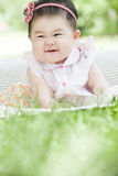 Portrait of smiling baby. An Asian baby is stting on grass and smiling innocently Royalty Free Stock Image