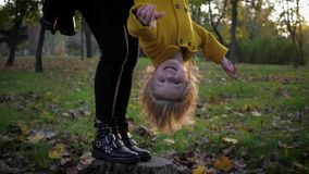 Portrait of a smiling baby girl hanging upside down in her mothers arms while walking in autumn park in the season of