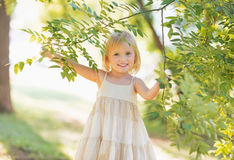 Portrait of smiling baby girl looking out from tree foliage Royalty Free Stock Photos