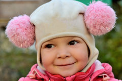 Portrait of a smiling baby girl in a pink hat Royalty Free Stock Images