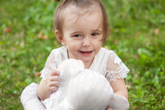 Portrait of smiling baby girl playing on grass with teddy bear Stock Photography