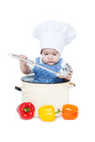 Portrait of a smiling baby sitting wearing a chef hat. Sitting inside a large cooking stock pot surrounded by vegetables Stock Photo