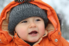 Portrait of smiling baby with snow in winter clothes Royalty Free Stock Image