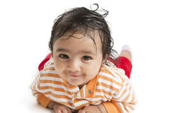 Portrait of a Smiling Baby on White Background. Portrait of a Smiling Baby Girl lying on her tummy on a White Background stock photography