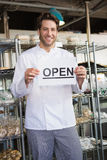 Portrait of a smiling baker holding open sign Stock Photography