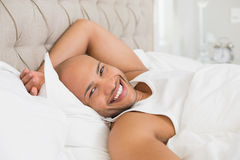 Portrait of smiling bald man resting in bed Stock Photo