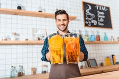 Bartender with refreshing lemonades. Portrait of smiling bartender holding glass jars with refreshing lemonades in hands in cafe Royalty Free Stock Images