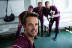 Portrait of smiling baseball team clicking selfie while standing at locker room. After match royalty free stock photography