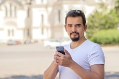 Portrait of a smiling bearded adult man with a smartphone on a city square in a sunny spring or summer day. Tourism and travel stock images