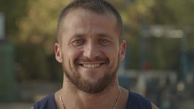 Portrait of smiling bearded athlete outdoors