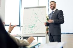 Mature Business Coach at Presentation. Portrait of smiling bearded business coach standing by whiteboard giving presentation for audience Stock Images