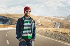 Portrait of a smiling bearded man standing on a country road against the backdrop of the mountains. The concept of. Traveling light stock image