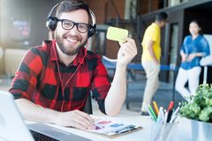 Modern Bearded Man in IT Office. Portrait of smiling bearded man wearing headphones and glasses showing blank green card while sitting at desk in modern office Royalty Free Stock Photos