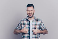 Portrait of smiling, bearded, perfect man showing two thumbs up. In checkered shirt over grey background Stock Photos