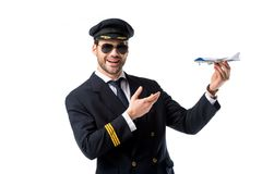 Portrait of smiling bearded pilot in uniform pointing at toy plane in hand. Isolated on white stock photo