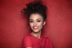 Portrait of beauty afro girl with toothy smile. Portrait of smiling beautiful african american young woman. Girl with afro.Red background. Studio shot Royalty Free Stock Photography