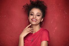 Portrait of beauty afro girl with toothy smile. Portrait of smiling beautiful african american young woman. Girl with afro.Red background. Studio shot Stock Photography