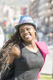 Portrait of smiling beautiful african woman with hat in the stre Stock Photography