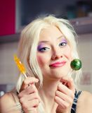 Portrait of smiling beautiful blonde girl with two candies in hands Stock Image