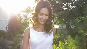 Portrait of smiling beautiful female in sunny weather close-up in beams. On nature stock footage