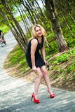 Portrait of a smiling beautiful girl in nature. In a black dress and red shoes Royalty Free Stock Images