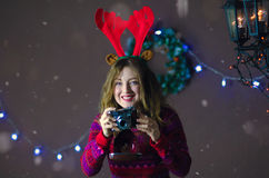 Portrait of smiling beautiful girl with reindeer horns making photos on background of Christmas decorations.  Stock Photo