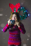 Portrait of smiling beautiful girl with reindeer horns making photos on background of Christmas decorations.  Stock Image