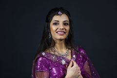 Portrait of smiling beautiful indian girl. Young female model wears jewelry sets and traditional purple clothes Royalty Free Stock Photo