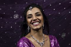Portrait of smiling beautiful indian girl. Young female model wears jewelry sets and traditional purple clothes Stock Images