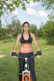 Portrait of smiling beautiful woman doing exercise with bicycle Stock Photo