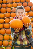 Portrait of smiling beautiful woman holding pumpkins on farm Stock Photography