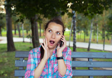 A portrait of a smiling beautiful woman in the park talking on t Stock Photo